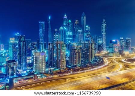 Scenic nighttime skyline of Dubai Marina, UAE. Futuristic skyscrapers of big modern city. Multicolored travel background. #1156739950