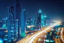 Scenic nighttime skyline of Dubai, United Arab Emirates. Aerial view on highways and skyscrapers in the distance.