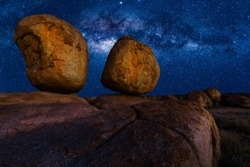 Scenic nocturnal australian outback landscape of Devils Marbles The Eggs by night with milky way, stars field and galaxies. Granite boulders of Karlu Karlu in Northern Territory, Central Australia.