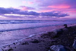Scenic ocean sunset in Carlsbad California. Colorful sunset at the beach. Soft focus. Waves in the water and purple pink sky.