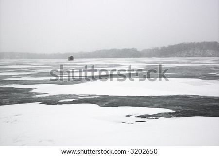 Scenic of frozen lake with ice fishing shack in Green Lake, Minnesota, USA.