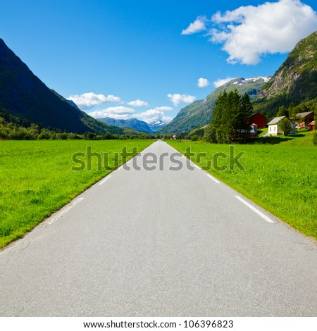 Scenic one lane asphalt road leads through mountain valley in Norway