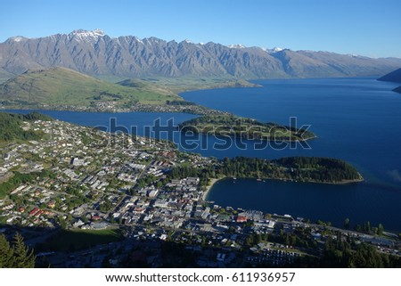 Scenic overview looking down on Queenstown, New Zealand with clear blue sky and South Island's Lake Wakatipu set against the dramatic Southern Alps #611936957
