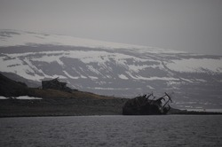 Scenic pan view of abandoned rusty fishing trawler with snowy mountains on background, Barents sea