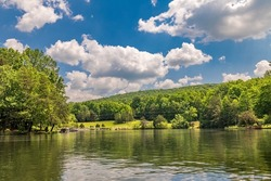 Scenic panorama of Lake Dartmoor in Tennessee shows a very calm, glassy lake surface with rich, healthy oak trees lining the shoreline.
