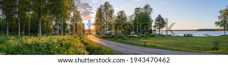 Scenic panorama of Swedish birch forest, summer village, lake and beautiful Sunset lighting on countryside road. Sweden. Foto stock ©