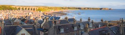Scenic panorama townscape view of the quaint seaside fishing village of Cullen Bay and viaduct during summer in Moray Scotland.