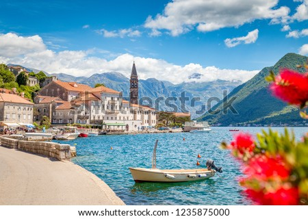 Scenic panorama view of the historic town of Perast at famous Bay of Kotor with blooming flowers on a beautiful sunny day with blue sky and clouds in summer, Montenegro, southern Europe