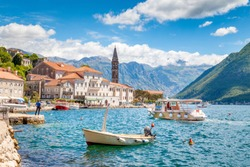 Scenic panorama view of the historic town of Perast at famous Bay of Kotor with boats on a beautiful sunny day with blue sky and clouds in summer, Montenegro, southern Europe