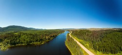 Scenic Panoramic Lake View of Curvy Road in Canadian Nature on a Sunny Summer Day. North of Prince George, John-Hart Highway, British Columbia.