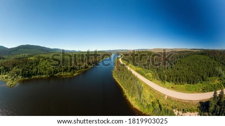 Scenic Panoramic Lake View of Curvy Road in Canadian Nature on a Sunny Summer Day. North of Prince George, John-Hart Highway, British Columbia. Foto stock ©