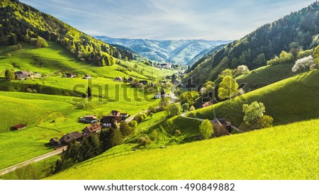 Scenic panoramic view of a picturesque mountain valley in spring with green hilly landscape, mountain forests and traditional houses. Germany, Black Forest. Colorful travel background.