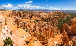Scenic panoramic view of famous Bryce Canyon National Park on a beautiful sunny day with blue sky and dramatic clouds seen from famous Sunset Point in summer, Utah, American Southwest, USA