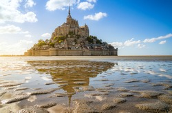 Scenic panoramic view of famous Le Mont Saint-Michel tidal island with historic abbey on top of impressiv rock on a beautiful sunny day with blue sky and clouds in summer, Normandy, northern France