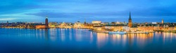 Scenic panoramic view of famous Stockholm city center with historic Riddarholmen in beautiful illuminated Gamla Stan old town district during blue hour at dusk, Sodermalm, central Stockholm, Sweden