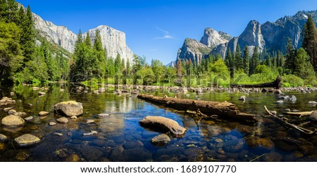 Scenic panoramic view of famous Yosemite Valley with El Capitan rock climbing summit and idyllic Merced river on a beautiful sunny day with blue sky in summer, Yosemite National Park, California, USA