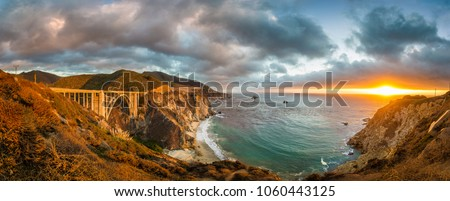 Scenic panoramic view of historic Bixby Creek Bridge along world famous Highway 1 in beautiful golden evening light at sunset with dramatic cloudscape in summer, Monterey County, California, USA