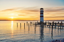 Scenic panoramic view of historic old Podersdorf Leuchtturm lighthouse at famous lake Neusiedlersee with beautiful cloudscape in idyllic golden evening light at sunset in summer, Burgenland, Austria