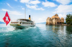 Scenic panoramic view of traditional paddle steamer excursion ship with historic Chateau de Chillon at famous Lake Geneva on a sunny day with blue sky and clouds in summer, Canton of Vaud, Switzerland