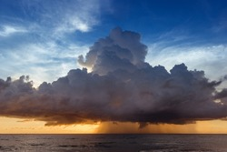 Scenic photo of beautiful sea sunset with yellow and blue sky and rain clouds