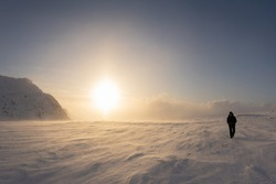 Scenic picture of large Sunset halo in winter mountains, selective focus because of strong snow drift wind. A person in black snowmobile overall and goggles walks against strong wind. Lapland Sweden