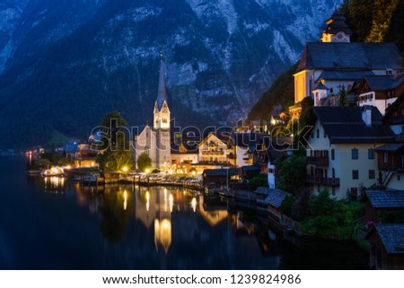 Scenic picture-postcard view of famous historic Hallstatt mountain village with Hallstattersee in the Austrian Alps in mystic twilight during blue hour at dawn in summer, Salzkammergut region, Austria