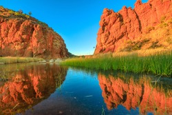 Scenic red rock formations of Glen Helen Gorge of West MacDonnell Ranges mirroring on calm waters of permanent waterhole in dry season at sunrise light. Northern Territory, Australian Outback.