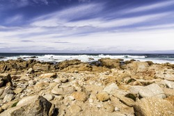 Scenic rocky coastline along the historic 17 Mile Drive in Pebble Beach California. Blue sky and sea, with white clouds.