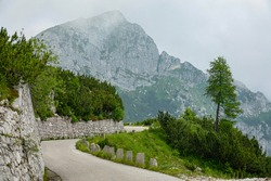 Scenic rocky mountains overlook an empty asphalt road running across the picturesque Julian Alps. Clouds and mist drift over the mountain pass and adjacent ridge high in the mountains of Slovenia.