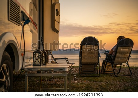 Scenic RV Campsite Pitch. Camper Van In the Recreational Vehicles Park. Woman Relaxing on a Chair and Watching Sunset Over the Sea.