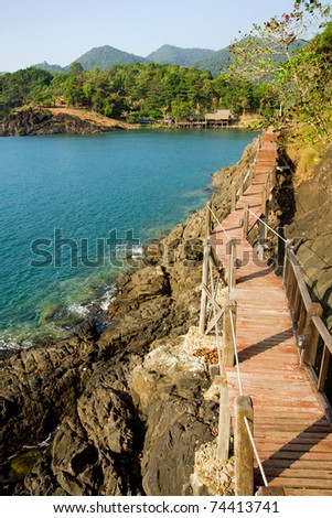 Scenic sea coastline of the Ko Chang island in Thailand with wooden path along the rocky shore