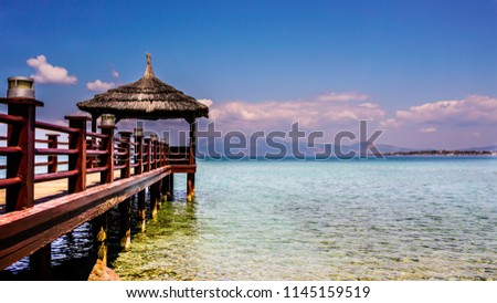 Scenic seascape and wooden pier view on Aegean Sea in Cesme / Turkey. A long coast pier under the clear sky. A quite, peaceful and calm holiday resort place in Bali / Asia. Path goes to freedom.