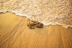 Scenic seascape. Foam wave approaching the stone at the beach. Sunset time. Waterscape for background. Selected soft art focus. Sunlight reflection on the water and sand. Balangan beach, Bali