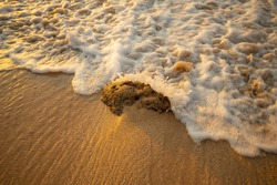 Scenic seascape. Foam wave splashing against the stone at the beach. Sunset time. Waterscape for background. Selected soft art focus. Sunlight reflection on the water and sand. Balangan beach, Bali