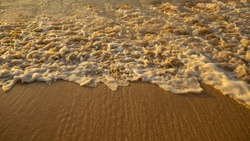 Scenic seascape. Milky foam waves at sandy beach. Sunset time. Waterscape for background. Selected soft art focus. Sunlight reflection on the water and wet sand. Balangan beach, Bali, Indonesia