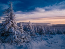 Scenic snowy landscape with a view from a mounatin range to the valley, snow, sky,clouds,sky,sunlight.Spruce trees with rime, scenic landscape. Jeseniky.Czech republic.