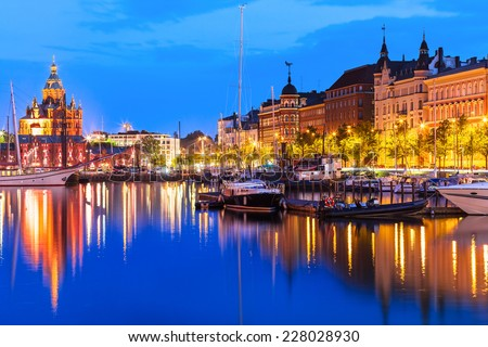 Scenic summer evening panorama of the Old Port pier architecture with tall historical sailing ships, yachts and boats and Uspenski Orthodox Cathedral in the Old Town in Helsinki, Finland