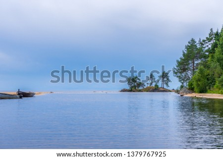 Scenic summer landscape with mouth of northern river flowing into lake in cloudy day. Travelling and discovering distant places of Earth. View from water. Chernaya river, Onega lake, Karelia, Russia #1379767925