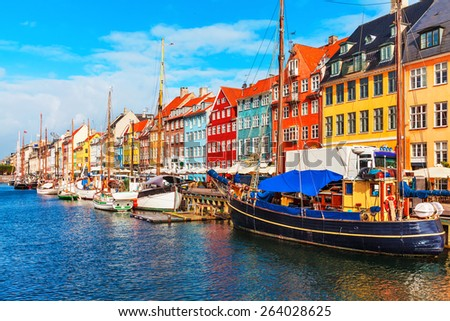 Photo of  Scenic summer view of Nyhavn pier with color buildings, ships, yachts and other boats in the Old Town of Copenhagen, Denmark