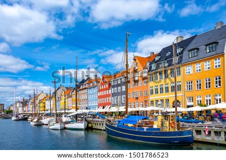 Scenic summer view of Nyhavn pier with colorful buildings and boats in Old Town of Copenhagen, Denmark