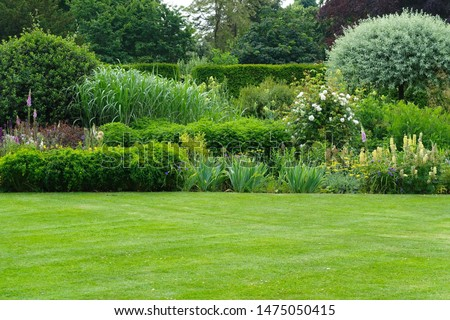 Scenic Summertime View of a Beautiful English Style Landscape Garden with a Green Mowed Lawn, Leafy Trees and Colourful Flower Bed
