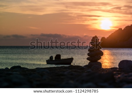 Scenic sunrise or sunset over sea surface, boat anchored in bay, Greece