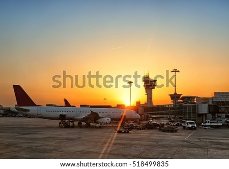 Scenic sunrise over airport airside apron with airport terminal building airplane silhouette parked to air bridge airport trucks air traffic control tower skyline view