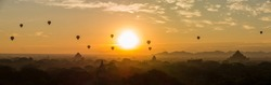 Scenic sunrise with many hot air balloons above Bagan and temples in Myanmar, Burma with mist and orange, yellow and red shining sun