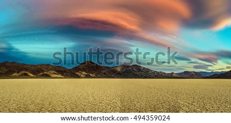 Scenic sunset at Racetrack Playa  in Death Valley National Park. The Racetrack Playa is a scenic dry lake with moving stones that inscribe linear imprints. Long exposure. #494359024