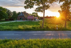 scenic sunset between trees and next to a vintage rural half timbered house in traditional style in the district Wesermarsch (Germany) during summer