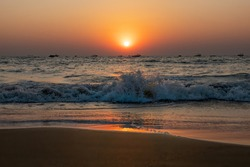 Scenic Sunset on beach in South Asia, white wave hitting sandy coastline. A lot of fishing boats on horizon line in Indian Ocean. Clear evening sky beautifully highlighted by orange red Sun