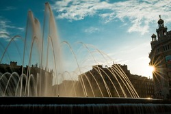 Scenic sunset view of Catalonia Square known as Plaza Catalunya in Barcelona with sun-rays and fountain. Placa Catalunya is a popular tourist spot and a city landmark