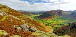 Scenic sunset view of Great Langdale valley in the Lake District, famous for its glacial ribbon lakes and rugged mountains. Popular vacation destination in Cumbria, North West England.