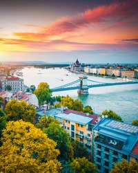 Scenic top view of the Hungarian Parliament and Chain Bridge on the Danube river at sunset. Location place Budapest, Hungary, Europe. Photo of popular tourist attraction of the world. Beauty of earth.